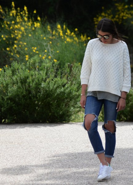 white cable knit sweater with ripped and cuffed blue jeans