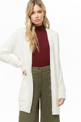 white fuzzy long cardigan with green mock neck ribbed sweater with wide leg pants