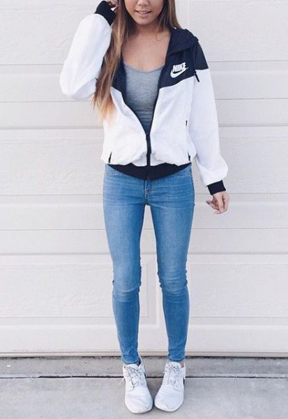 white windbreaker with grey form fitting tank top and blue skinny jeans