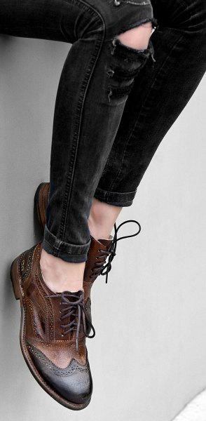 black ripped skinny jeans and brown leather wingtip shoes