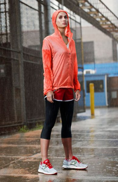 red windbreaker with black cropped leggings and grey sneakers