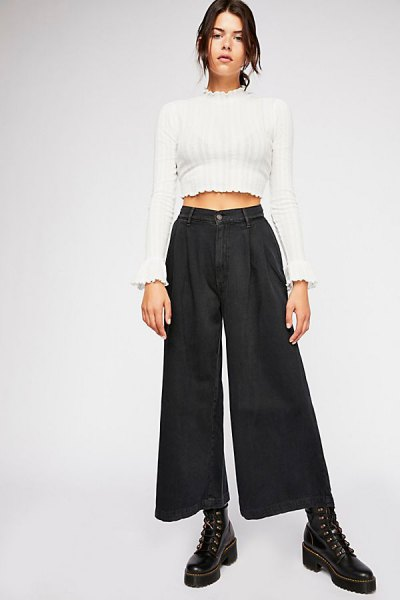 white mock neck cropped sweater with black pleated jeans