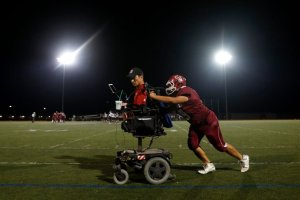 San Jose High School varsity quarterbacks coach Rob Mendez gets a push from xx (29) after the battery in Mendez's wheelchair died in the second quarter of their game against Ann Sobrato High School at San Jose High in San Jose, Calif., on Friday, Nov. 4, 2016. (Nhat V. Meyer/Bay Area News Group)