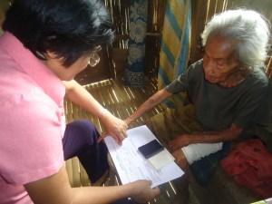 A beneficiary of the Social Pension receives her quarterly pension.