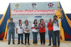 Alani Asid, 41 receives the symbolic key which marks the formal turn over of  their new homes in Taluksangay,Zamboanga City