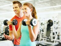 Portrait of handsome coach training woman with dumbbells at gym