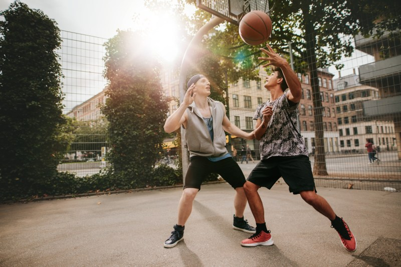 Teenage friends playing basketball against each other on an outdoor court. Two young men playing a game of basketball.