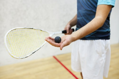 squash racket and ball in men's hand. Racquetball equipment