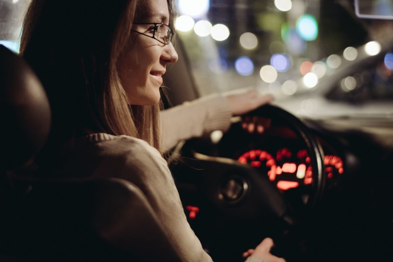 Woman driving car by night in the city