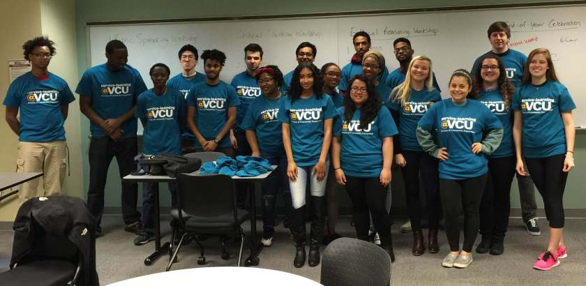 """Photograph of VCU students standing in front of a white board, wearing """"Service Learning at VCU"""" tee shirts."""