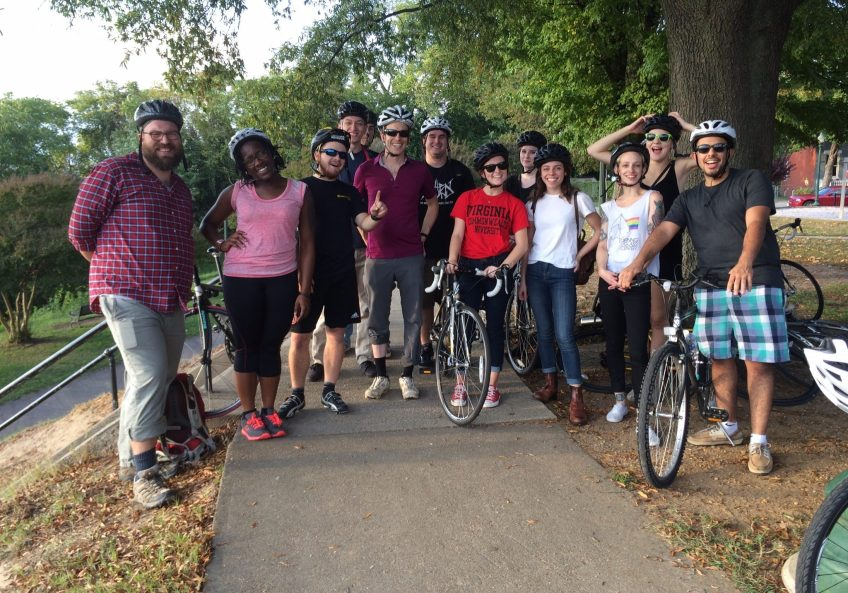 Photograph of Focused Inquiry Undergraduate Teaching Assistants standing with mentors Thad Fortney and Peter Henry in a park. Students have bicycles and wear bicycle helmets.