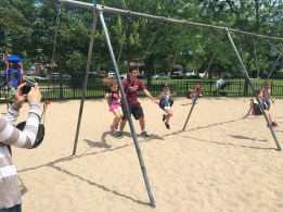 Campers playing at on the swing set at the Dovercourt Park playground