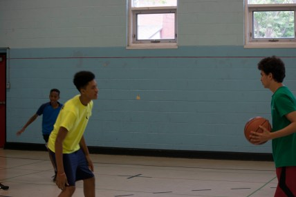 Camp staff and camper enjoying a competitive game of basketball