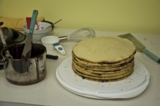 the cake in the process of being iced, with pot, spatuala and other tools