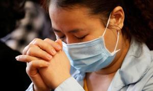 China anuncia fim do pico do coronavírus enquanto orações continuam