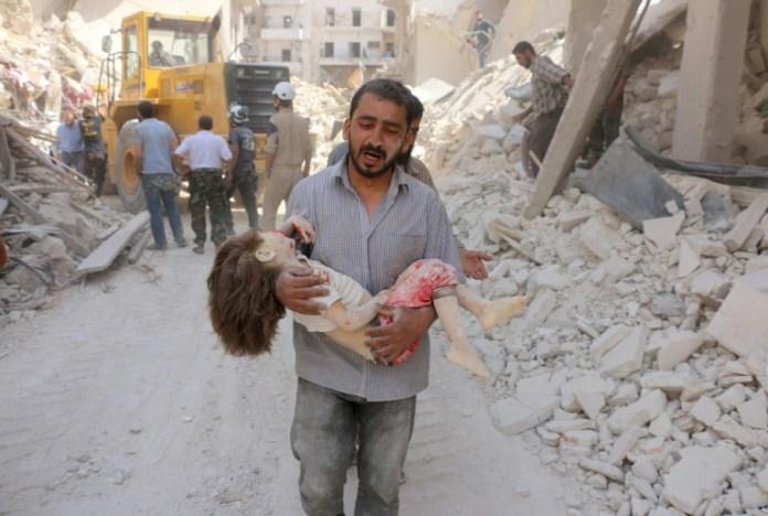 Um homem sírio carrega o corpo de uma criança após ataque aéreo do regime sírio, em Aleppo