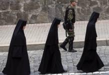 Irmãs ortodoxas caminham ao lado de um policial na Ucrânia