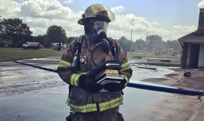 Bombeiro segura as Bíblias que foram resgatadas intactas do incêndio.
