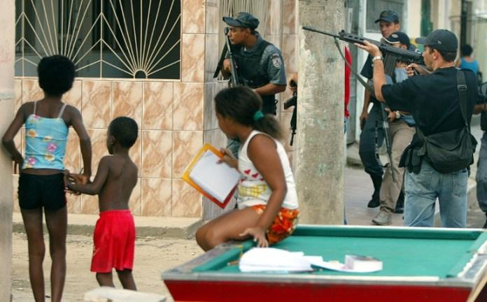 Policiais armados perto de crianças em uma favela