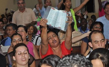 Cristãos participam de culto em Cuba, enquanto uma das fiéis expõe sua Bíblia. (Foto: United Bible Societies)