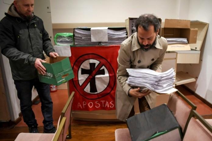Ativistas organizam folhas com asssinaturas dos que renunciam à sua filiação à Igreja católica na Argentina em Buenos Aires em 24 de agosto de 2018