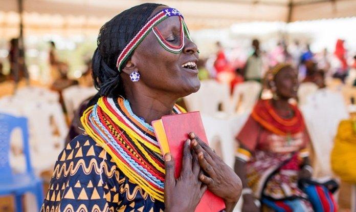 Mulher Rendille coloca Novo Testamento traduzido para seu idioma perto do coração. (Foto: Esther Havens)