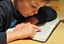 Criança lendo a Bíblia na escola
