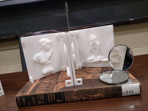 3D book and the book Notre Dame de Paris by Victor Hugo and a small round compact mirror