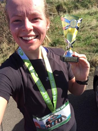 Ellie Hayes smiles and holds up her trophy for 1st lady at the Whitstable 10k