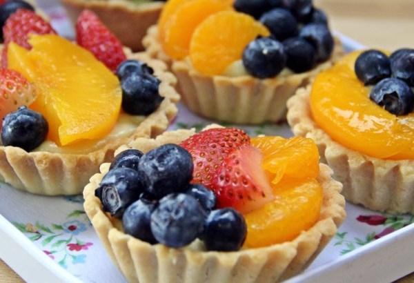 Søte terter med vaniljekrem bær og frukt