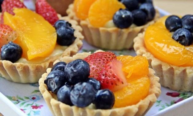 Søte terter med vaniljekrem, bær og frukt
