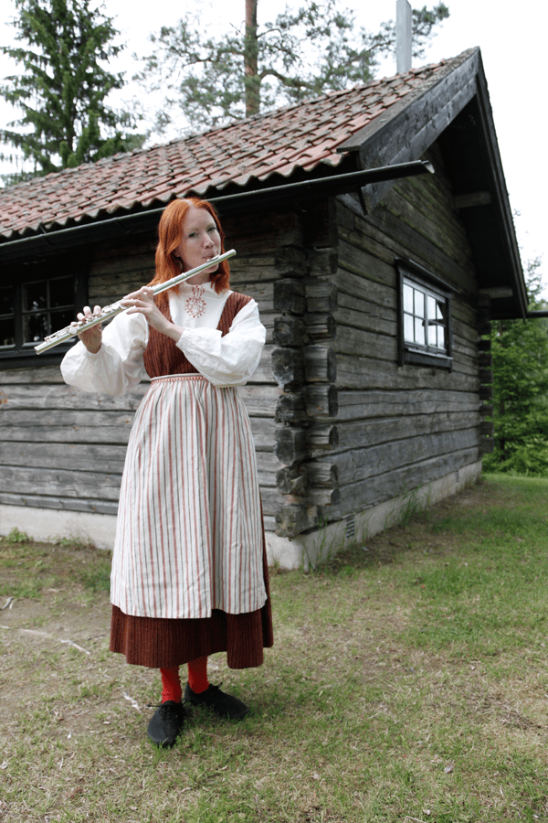 Åsa Larsson, aka Resmiranda, playing the flute in traditional dress.