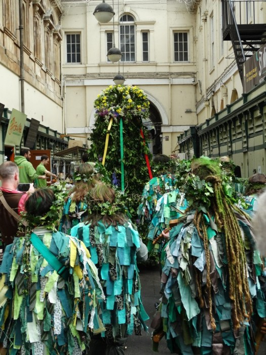 A group of people in green costumes following the Jack-in-the-Green in a Bristol street