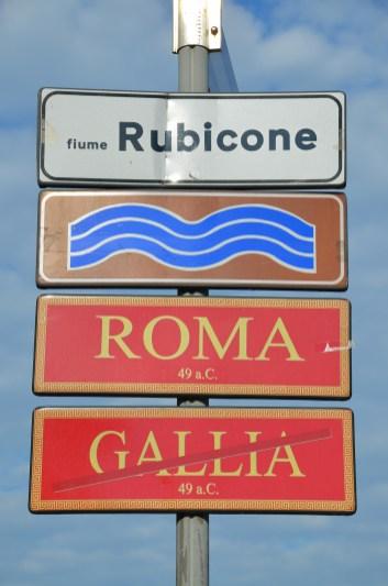 Street signs marking the limit of Julius Caesar's province, Roman bridge over the Rubicon river, Savignano sul Rubicone, Italy