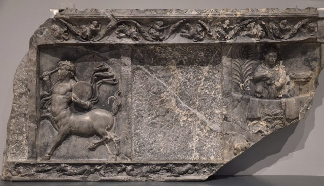 Fragment of a marble panel with depiction of a musician centaur with thyrsus and drum and a herm of Herakles (Dionysiac subjects).