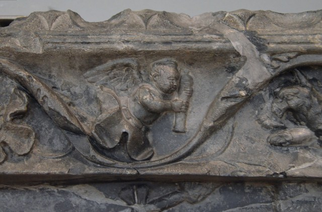 Detail of the upper part of the marble relief with cupids hunting.