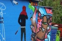 """Awesome concept - someone spray painted a mural of a guy """"covering up"""" another spray painted mural"""