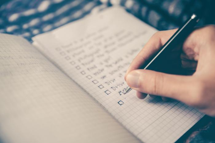close up of a hand writing a checklist  on grid paper from a meeting to plan for marketing strategy