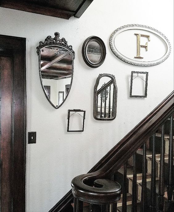 gallery wall with old mirrors and frames painted stairs