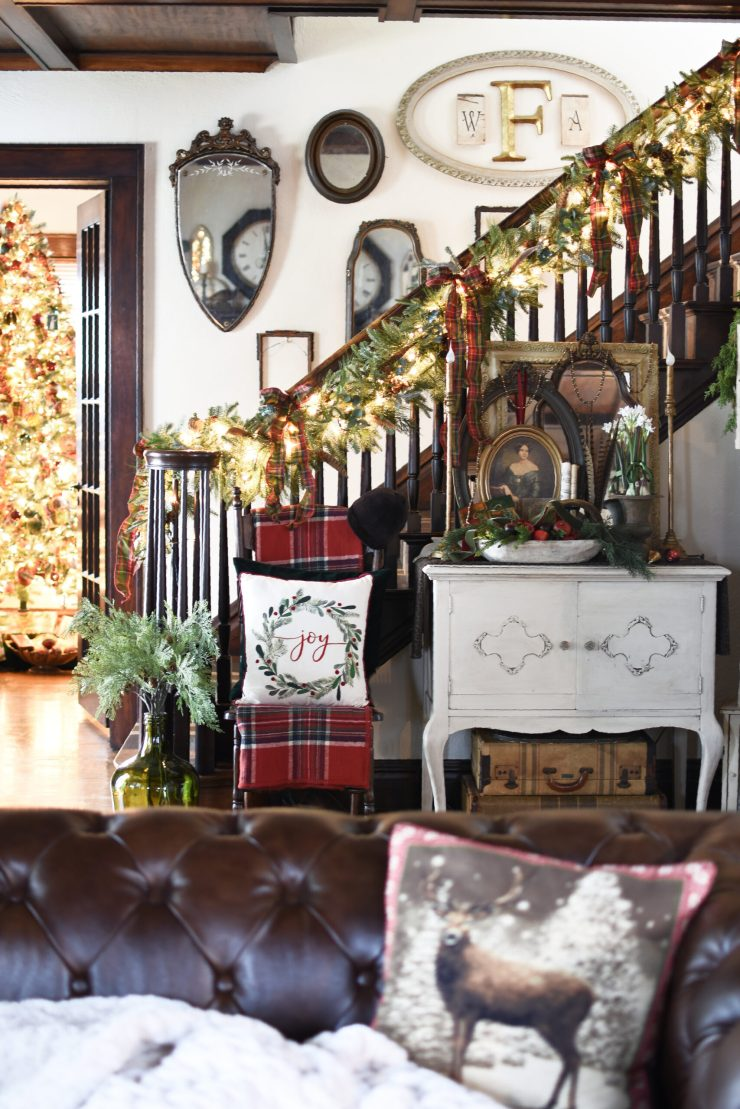 Christmas Entry Christmas Staircase traditional Christmas decorating with plaid, evergreens, pheasant feathers. Red, green and gold Christmas decorating. English Country Christmas and Victorian Christmas decorating with antiques and vintage #victorianChristmas #plaidChristmasdecor #Christmasstaircase