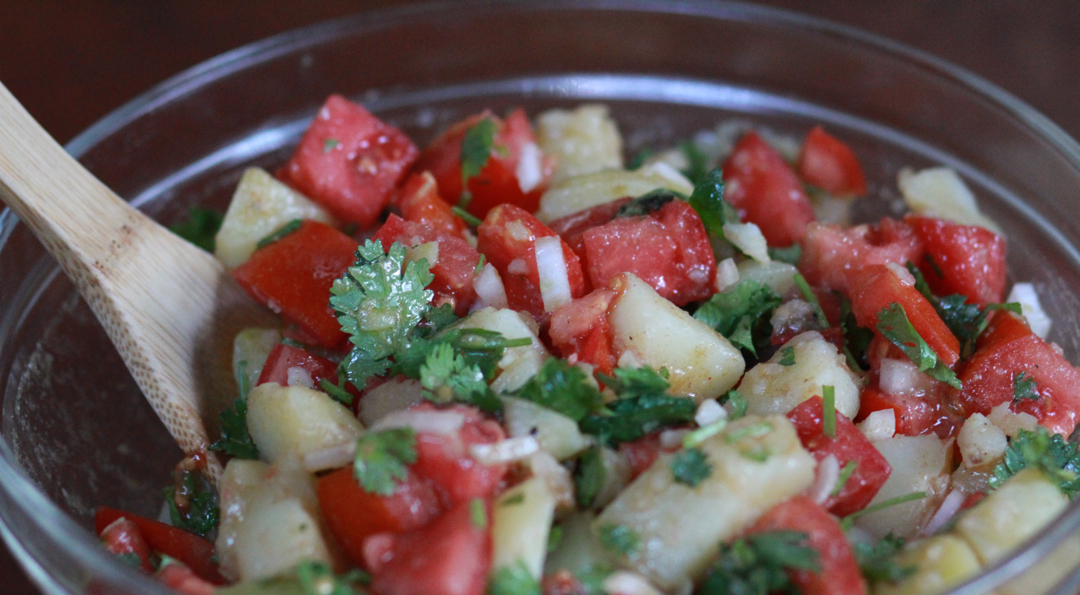 potato salad with cubed tomatoes, onions and cilantro