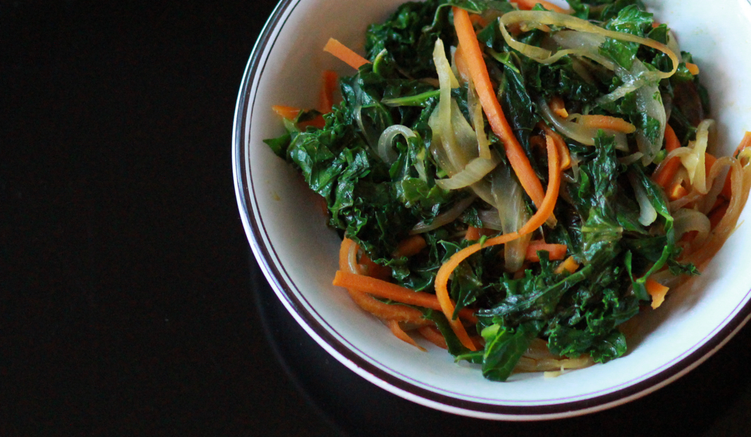 a bowl with kale sauté and carrots on black background