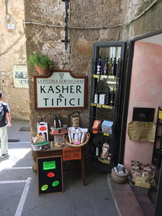 A sign showing Kasher & Tipici products in Pitigliano