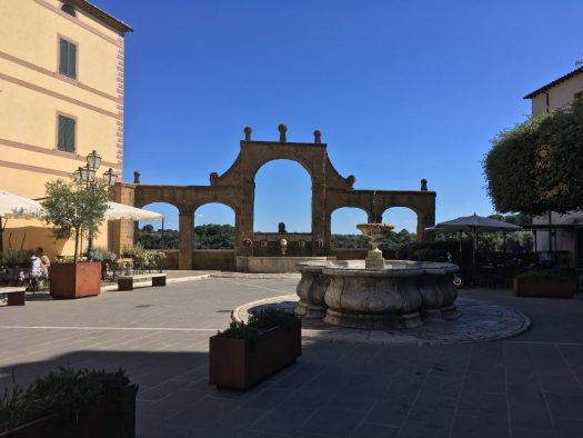 Picture of an aqueduct-like construction on an Italian square with a fountain in the middle