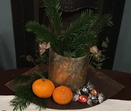 Picture of a foraged wild bouquet (with tree branches, chocolates and tangerines)