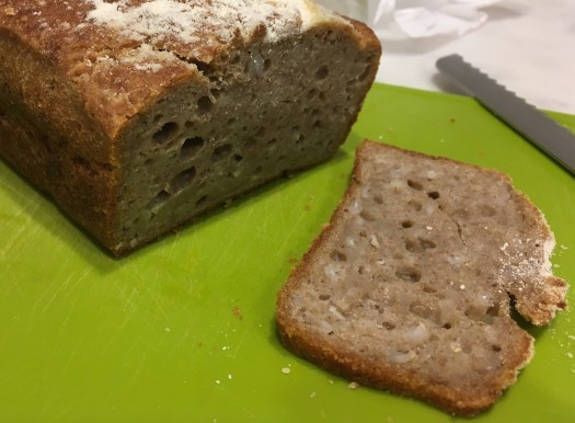 Image showing a loaf of dark rectangular bread, and a slice of the loaf