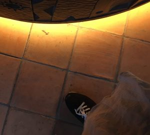My foot over the earth tiles on the reception area