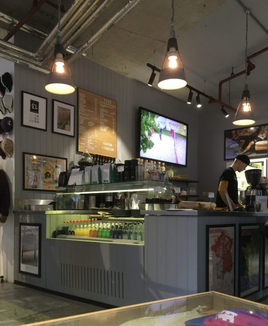 Picture of Rapha café interiors, depicting a café counter, with a lower fridge housing drinks; the café menu, a TV displaying cycling videos and cycling memorabilia on the walls, and a barista operating a coffee machine