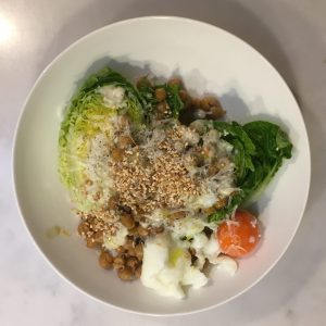 Gem lettuce with fried chickpeas, sesame seeds, a soft boiled egg, and tahini sauce