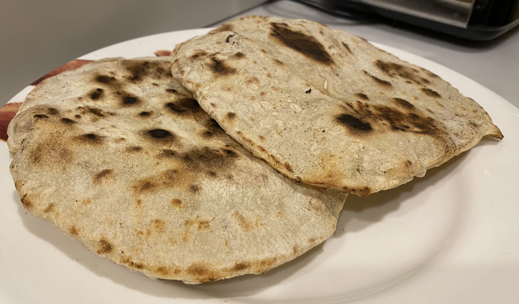 Two pitta breads with charred bits, slightly puffed up, on a plate